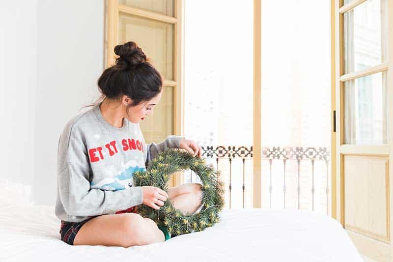 mujer decorando un balcón pequeño en navidad
