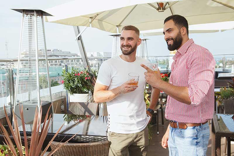 dos hombres beben en una terraza acristalada con paraviento de terraza