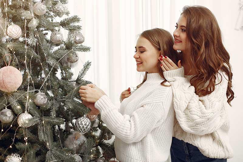 chicas decorando un arbol de navidad en balcon